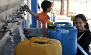 UNWRA - Two children fill up bottles of water to take home.