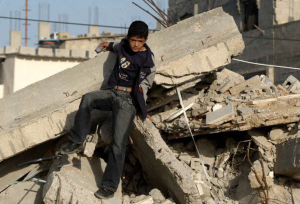 UNRWA  -  A boy hangs on to what is left of his house after the 2008-09 Israeli military incursion into Gaza.