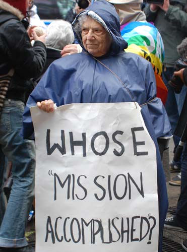 "Molly with sign, ""Whose Mission Accomplished"""